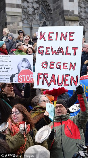 A man holds up a sign reading 'No violence against women' as he takes part in a demonstration in front of the cathedral in Cologne. On New Year's Eve 2015, there were sex attacks by migrants in the city