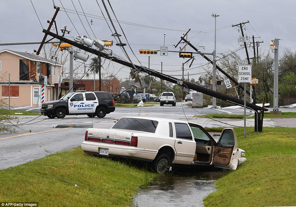 An abandoned car sits in a ditch in Rockport beneath toppled electricity pylons and damaged traffic lights