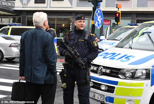 A police officer carrying an assault rifle talks to a member of the public during the lockdown of Medborgarplatsen Square