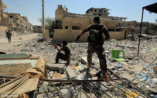 Un miembro de las Fuerzas Democráticas Sirias mantiene la guardia mientras sus compañeros corren para ocultarse frente a la posición de los combatientes del Estado Islámico en Raqqa, Siria el mes pasado