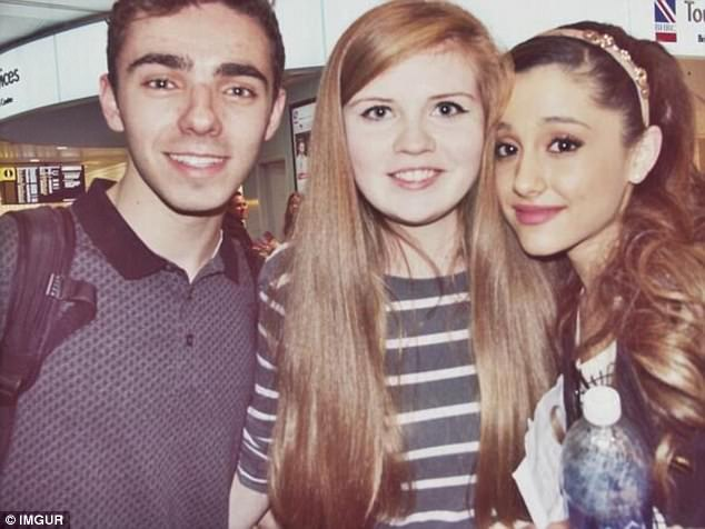 This lucky fan is pictured at London's Heathrow Airport with Ariana Grande (right) and The Wanted's Nathan Sykes (left)
