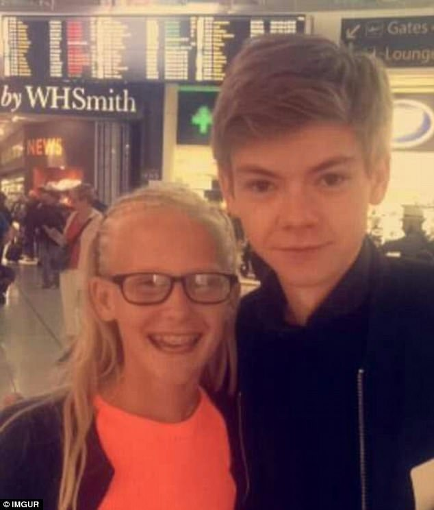 Thomas Brodie-Sangster (right) with a fan (left), pictured at Heathrow Airport, where he starred in a major scene for the 2003 hit Love Actually