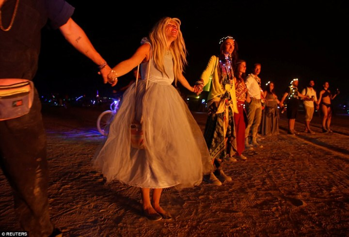 Participants surround a burning art installation as approximately as they enjoy festivities at the Burning Man festival in Nevada