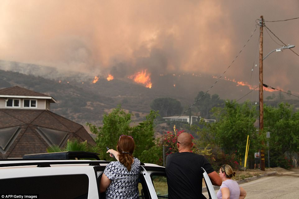 People watch flames of La Tuna Fire blaze on a hill in the Shadow Hills neighborhood Saturday. Smoke completely fills the sky