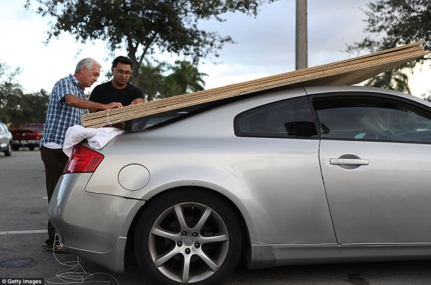 Luis Lorenzo (left) and Jairo Ruiz (right) purchase plywood at The Home Depot as they prepare for Hurricane Irma on Wednesday in Miami, Florida