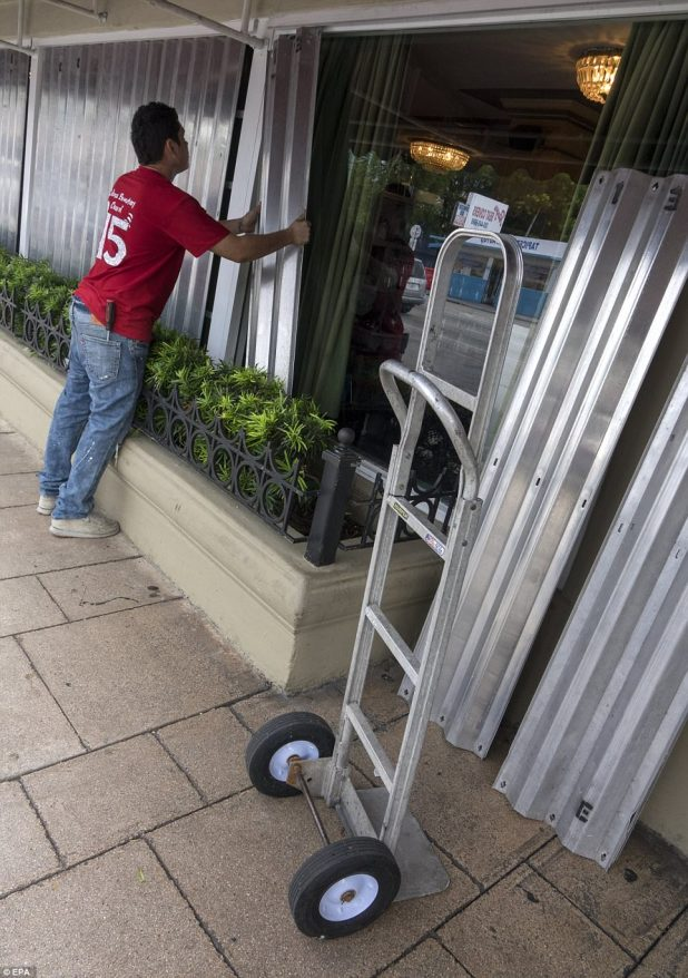 A worker installs shutter panels to protect the windows of the 'Versailles' restaurant as preparations for the advancing Hurricane Irma in Miami, Florida on Wednesday