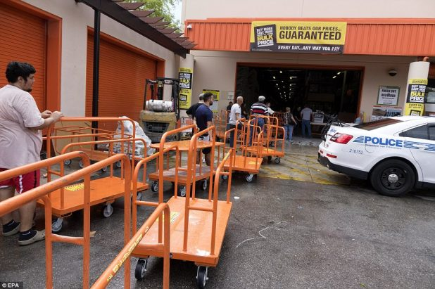 Customers line up with large carts to buy plywood from a Home Depot in Miami, Florida on Wednesday