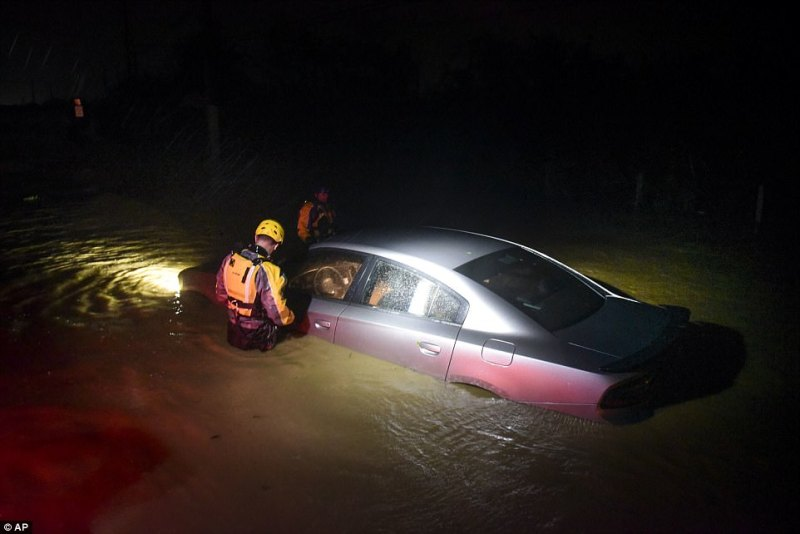 Irma passed to the north of Puerto Rico late on Wednesday night lashing it with heavy rain and powerful winds. Rescue crews are pictured above investigating a flooded car in Fajardo, Puerto Rico