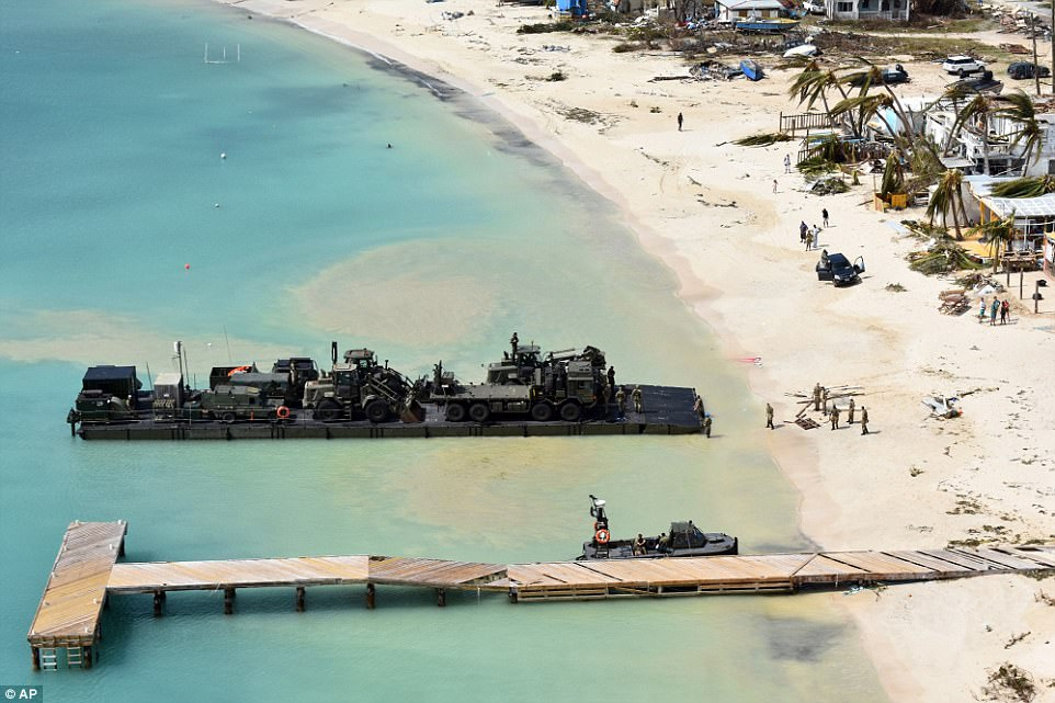 In this undated photo provided by the British Ministry of Defence on Friday taken from a Royal Navy helicopter, a RLC Mexeflote approaches Sandy Bay Village beach, in the British oversees territory of Anguilla loaded with the 2 JCBs, 1 flatbed lorry, fork lift truck, BV 206 multi terrain vehicle, a Land Rover and a mobile generator