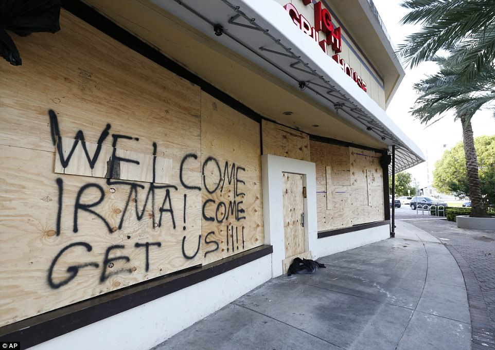 A message to Hurricane Irma is written on the facade of a boarded restaurant on Friday in Miami Beach, Florida