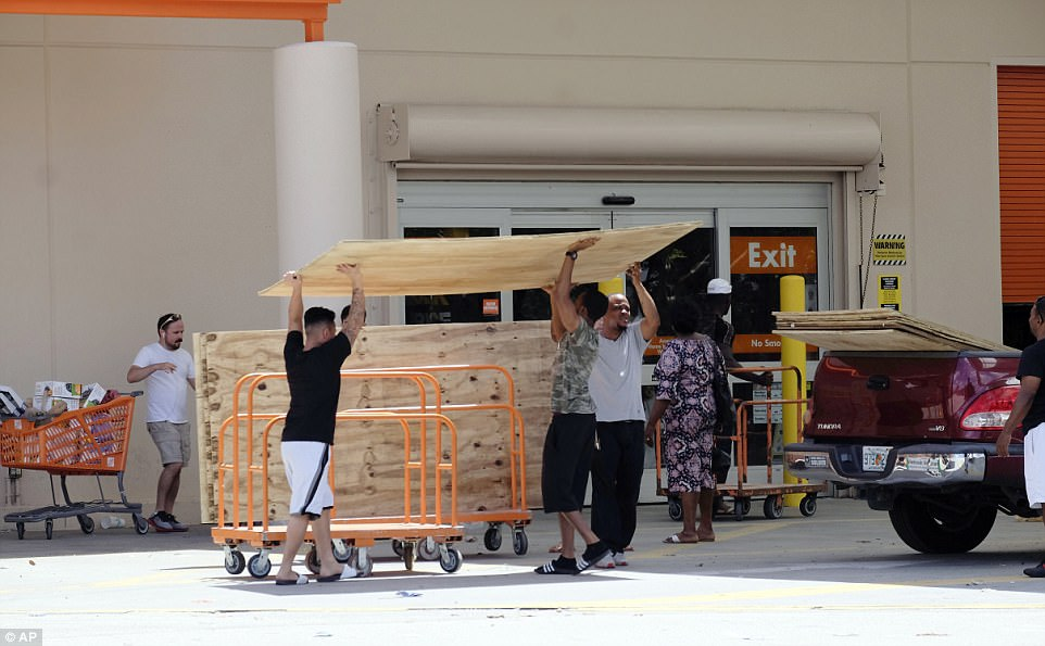 Customers buy plywood sheets to protect their homes at a Home Depot in Florida City, Fla., Friday, Sept. 8, 2017