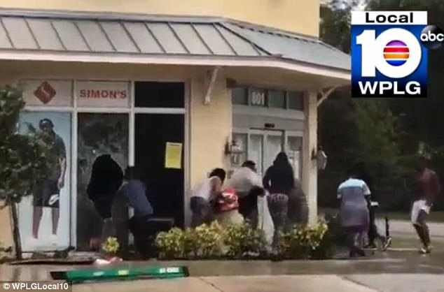 None of the group of at least eight people have been identified. They were filmed entering the store through a broken window and leaving with store merchandise