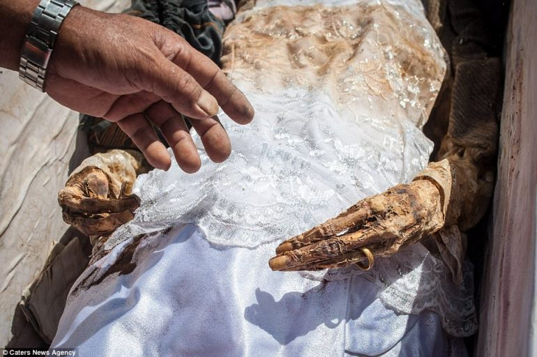 A villager called Minangga cleans the body of his mother Tumba, who died in 2004 and was buried in her wedding dress