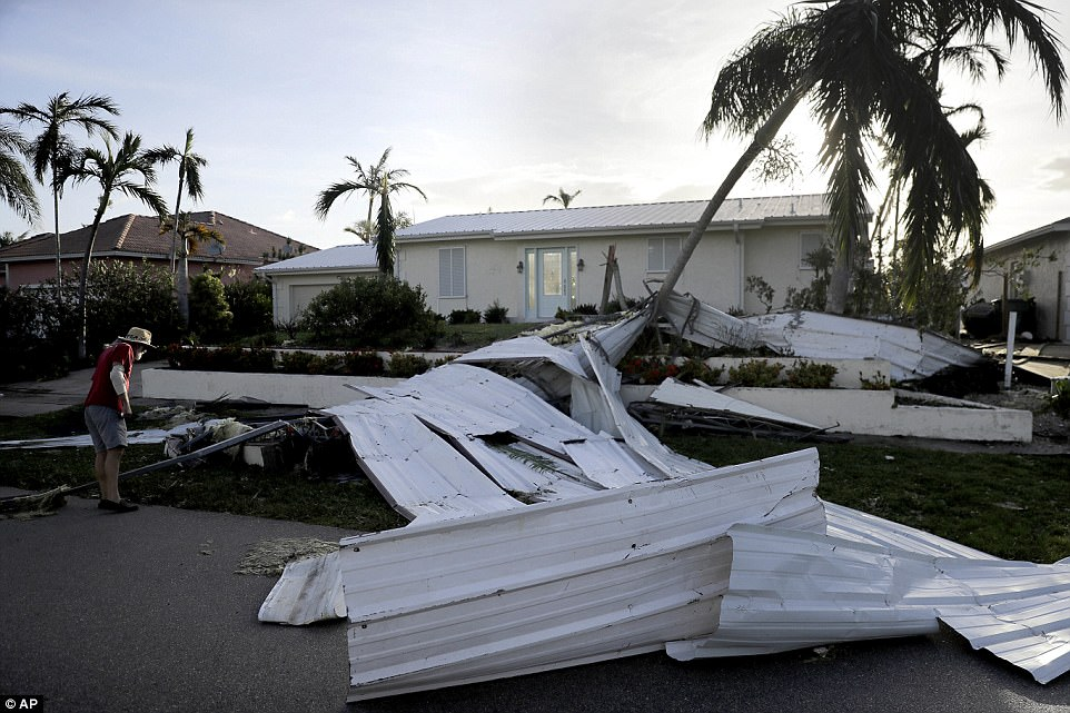 A roof is strewn across a home's lawn as Rick Freedman checks his neighbor's damage from Hurricane Irma in Marco Island, Florida on Monday
