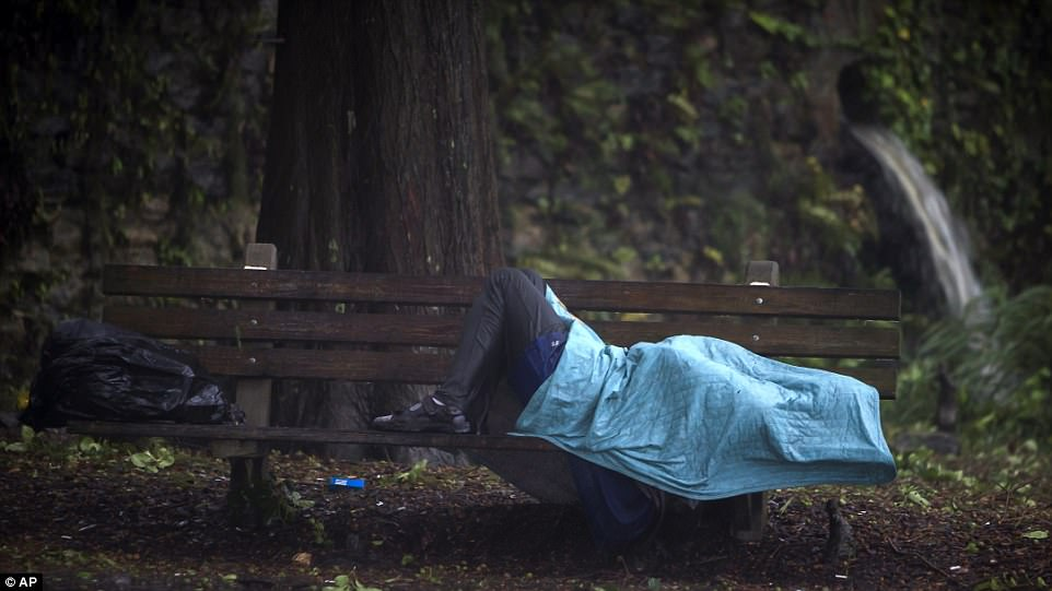 A homeless man lays on a bench on Historic River Street on Monday in Savannah, Georgia