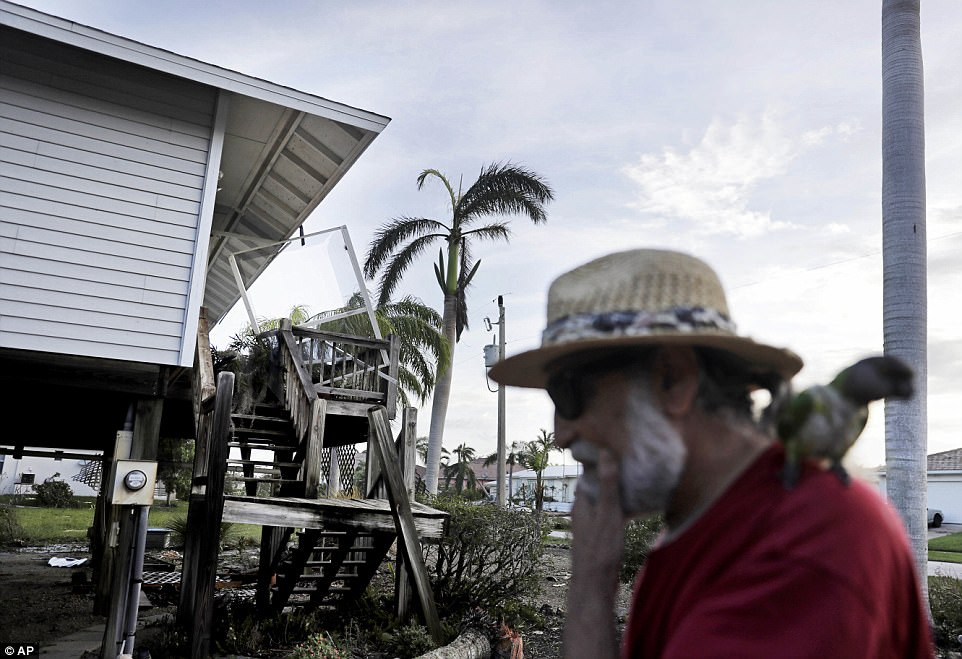 The front staircase sits damaged as Rick Freedman surveys the aftermath on his home with his parrot Mango from Hurricane Irma in Marco Island, Florida on Monday