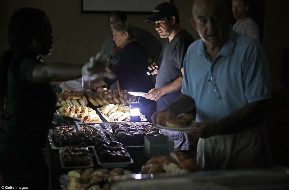 Hotel guests are served breakfast by lamplight as the power remains off at the Courtyard by Marriott one day after Hurricane Irma struck the state on Monday in Fort Lauderdale, Florida