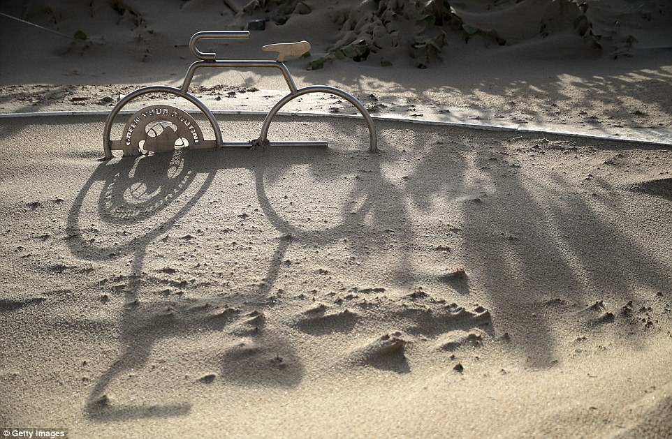 A bicycle rack is half buried in blown sand at Fort Lauderdale Beach the day after Hurricane Irma slammed into the state on Monday