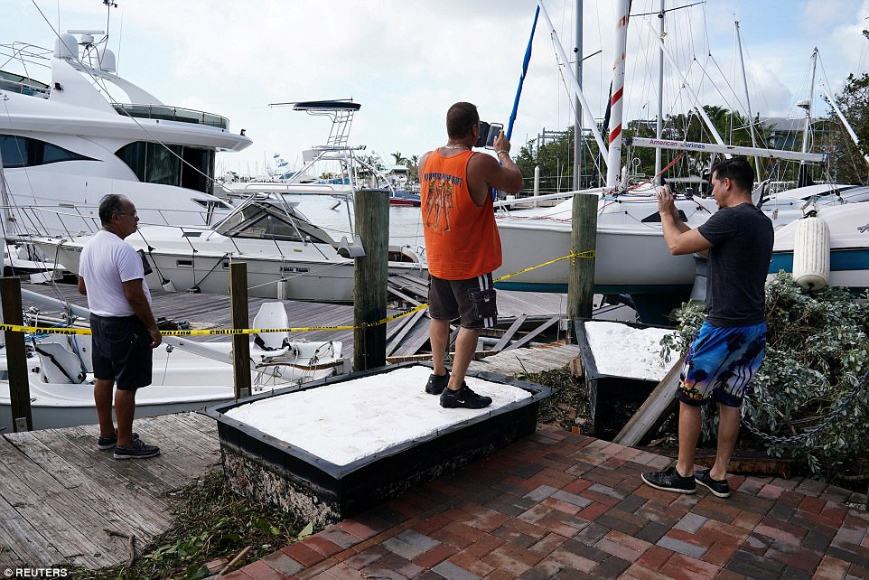 People take photos of boats that have come ashore in Coconut Grove following Hurricane Irma in Miami, Florida, on Monday