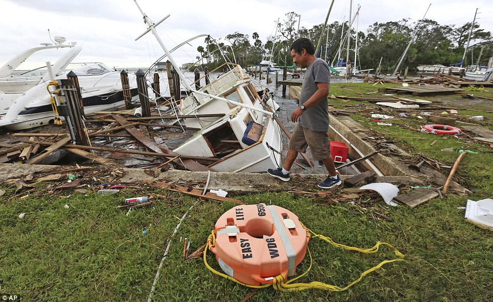 A man walks by damage from Hurricane Irma at Sundance Marine in Palm Shores, Florida, Monday, September 11, 2017