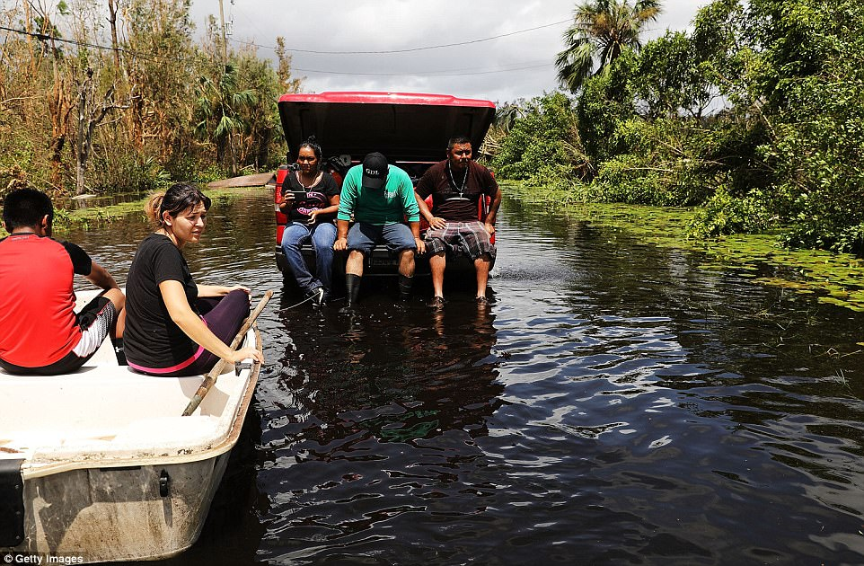 A family leaves their flooded home in a rural area the morning after Hurricane Irma swept through the area on September 11, 2017 in Naples, Florida