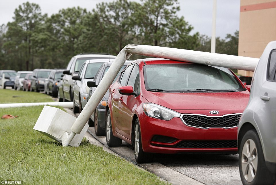 A lamp post is wrapped around a car in the wake of Hurricane Irma in Kissimmee, Florida September 11, 2017