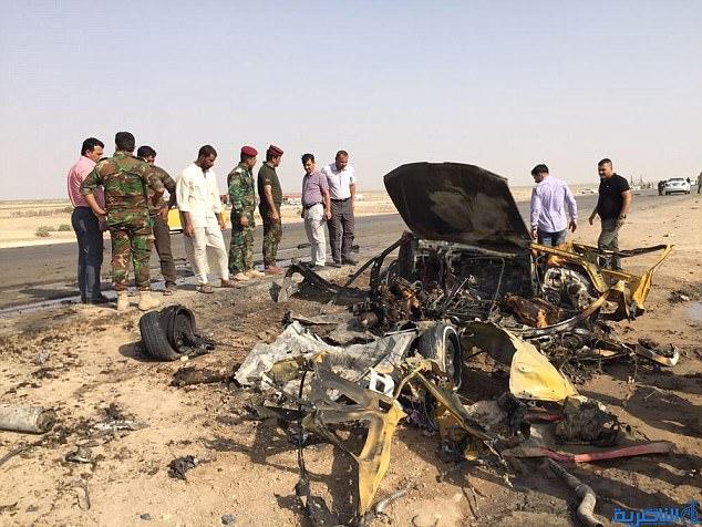 Atentados suicidas: Oficiales militares y testigos están al lado de lo que queda de uno de los coches usados por terroristas para atacar un puesto de control policial en una carretera cerca de Nassiriya