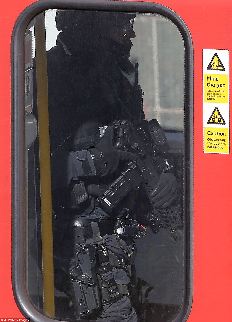 A heavily armed officer wanders through the damaged train's carriages looking for more devices
