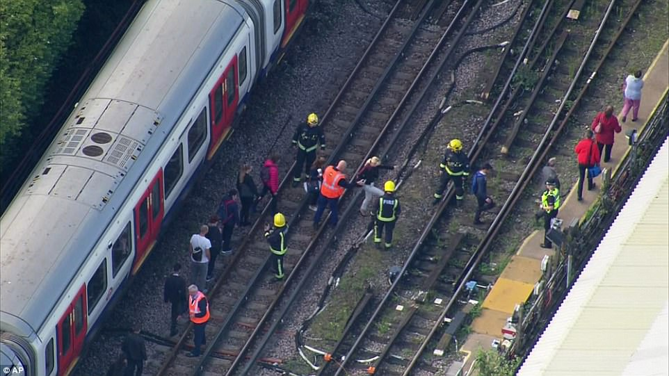 Passengers are ushered across the track by firefighters after getting trapped in the aftermath of the bombing