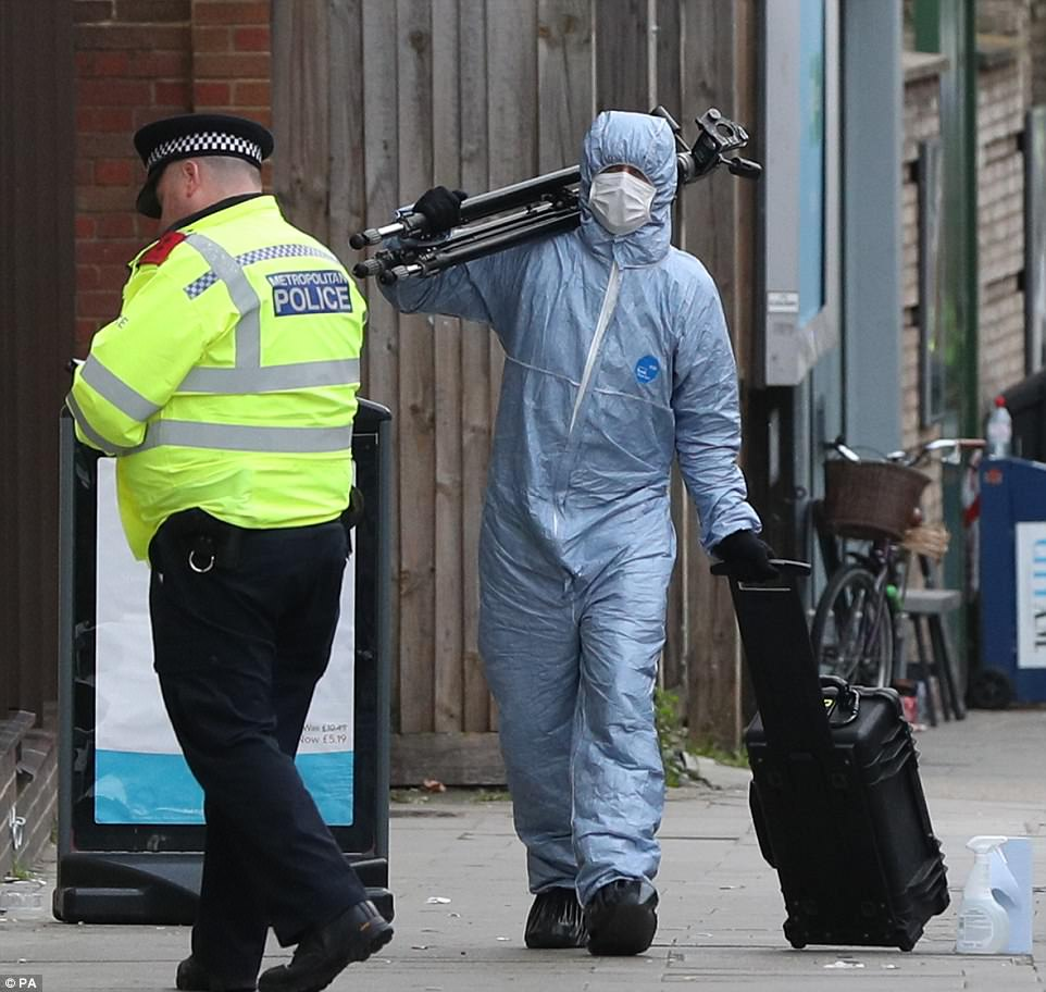 A forensic officer in blue overalls walks along the pavement near Parsons Green tube station as the investigation continues into the attack