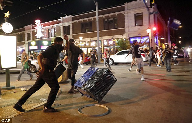 People overturn trash cans and throw objects as police try to clear a violent crowd Saturday