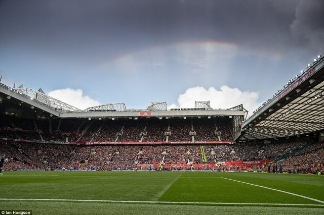 A rainbow hangs over the stadium following the shower at the start of the contest during an evenly contested encounter