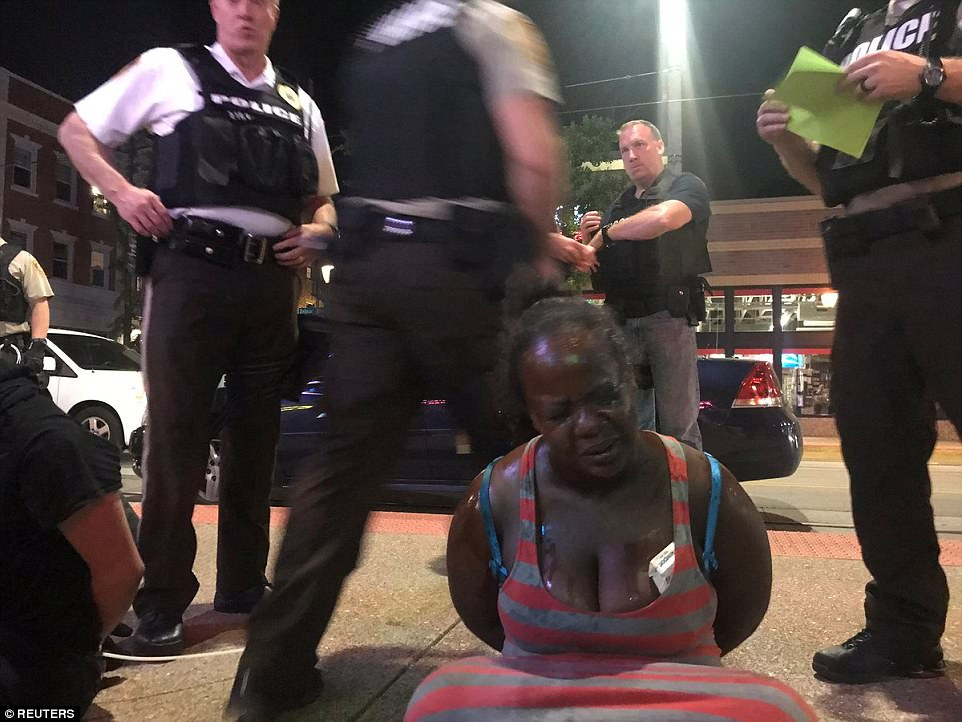 A protester is seen being arrested in St Louis following riots on Saturday night, which saw dozens of shopfronts smashed. The violence broke out after a peaceful protest concluded earlier Saturday