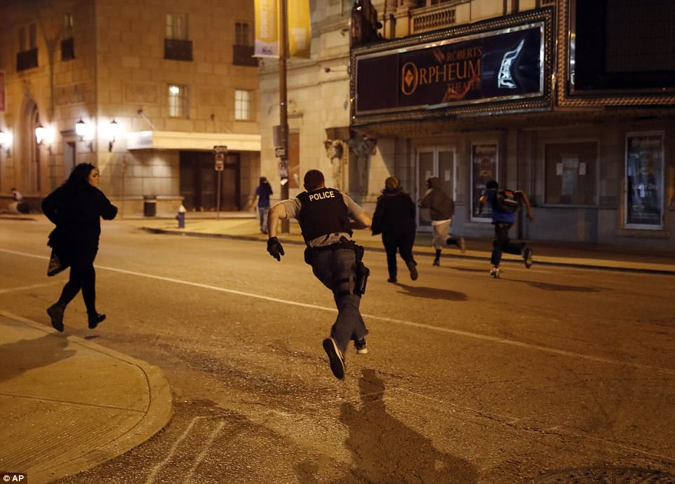 A cop chases after vandals in downtown St Louis on Sunday. Residents remain angry about the Stockley decision - but rioters may turn public opinion against protesters if they continue