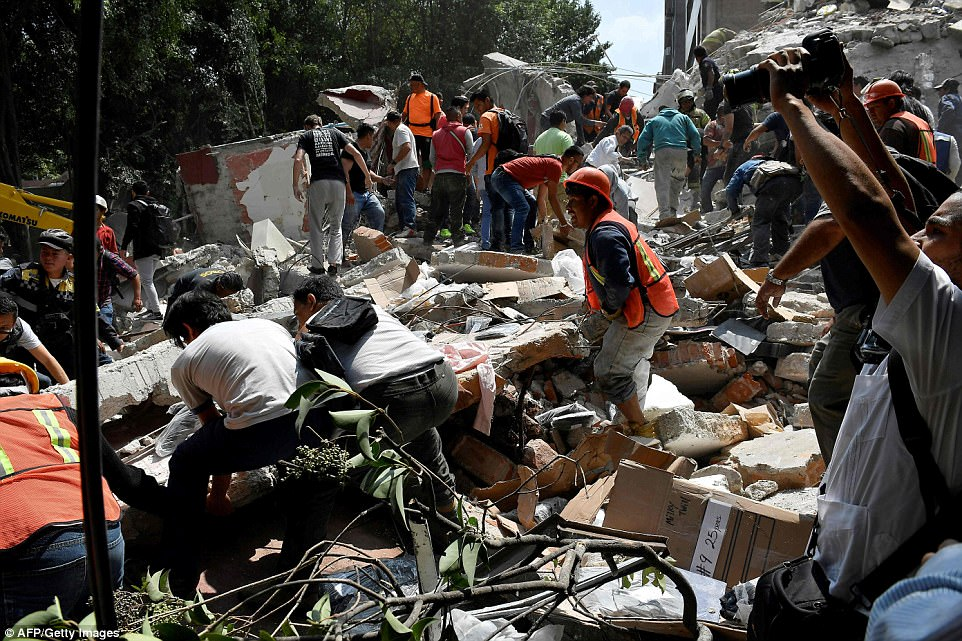 Rescuers are seen working through piles of debris in Mexico City with the help of bystanders