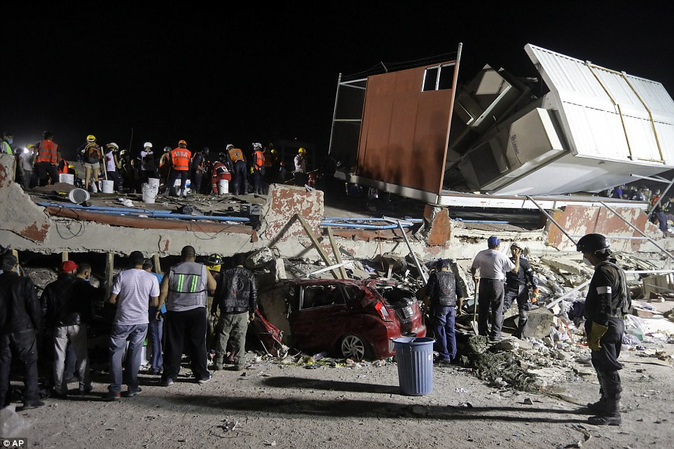Rescue personnel and volunteers work on a four-story building that collapsed after an earthquake in Mexico City