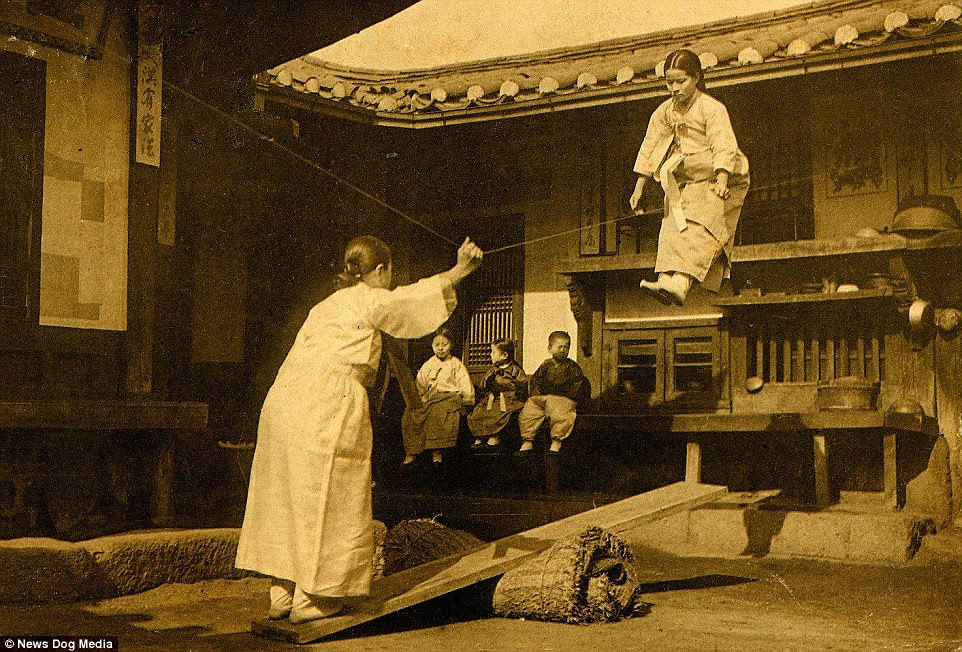 Taking flight: A young woman flies through the air as she plays the dangerous see-saw game of Neolttwigi with a friend between 1900 and 1905 at an unknown location in Korea