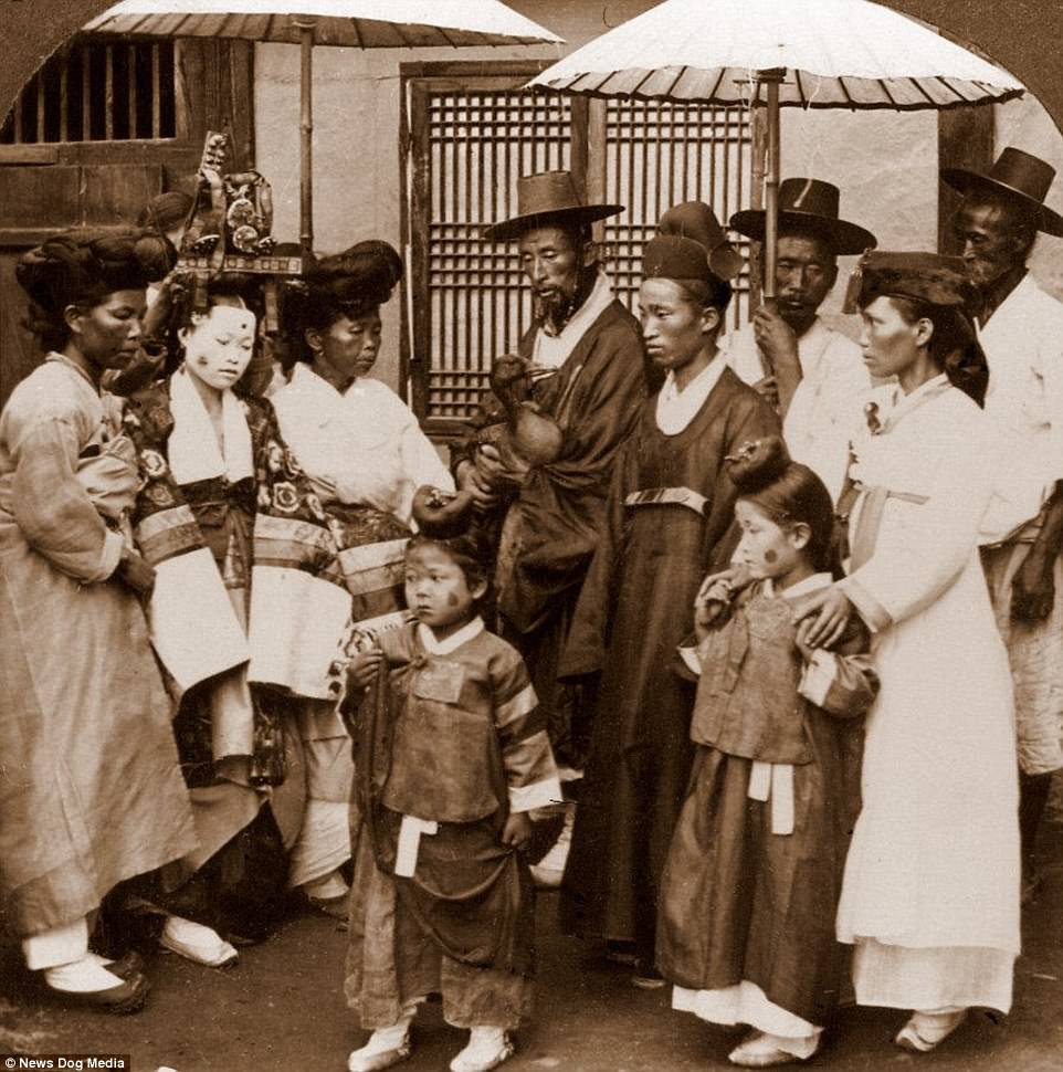 Stunning photographs have emerged showing a forgotten time when Korea was unified and people were free to live in peace without the threat of nuclear war. This image shows guests with face paint attending a wedding in Seoul, the capital of what is now South Korea, in about 1900