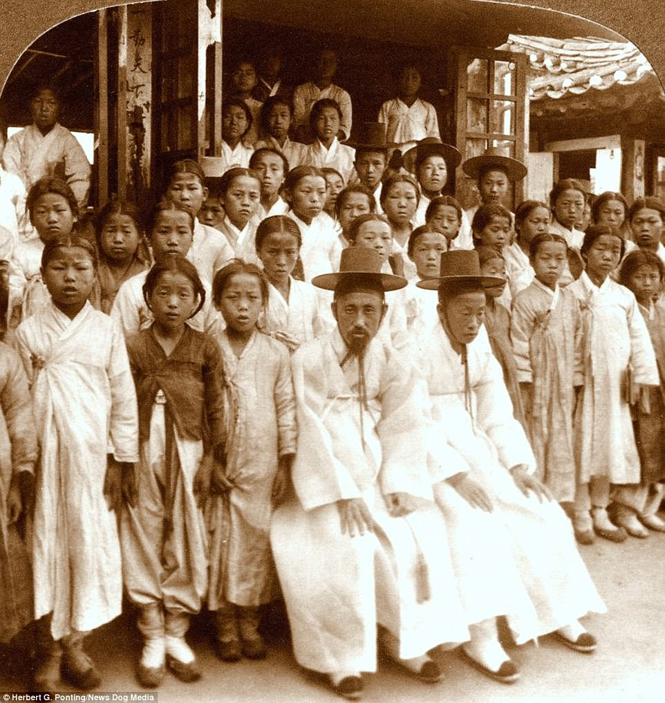 Taken between 1890 and 1910 before the Korean War tore a nation apart, the people of the north and south can be seen living together in harmony. This image shows a school in Seoul, Korea in 1903. The three boys in the back wearing hats are married