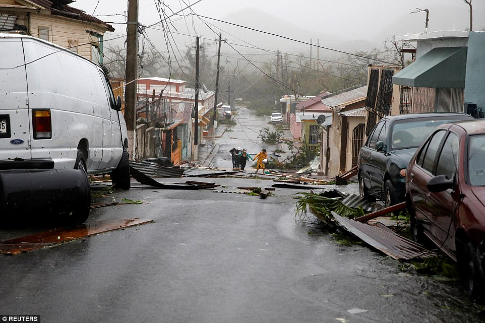 People walk on the street next to debris after the area was hit by Hurricane Maria in Guayama, Puerto Rico on Wednesday