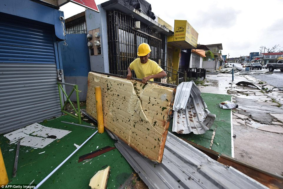 Isidro clears his yard of debris left by the passage of Hurricane Maria, in San Juan, Puerto Rico on Wednesday