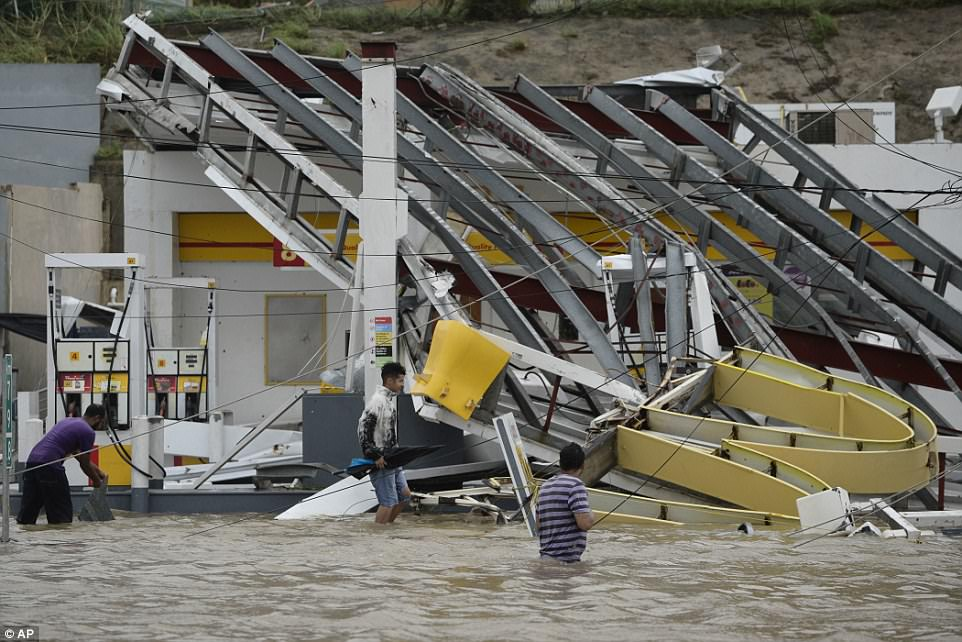 People walk next to a gas station flooded and damaged by the impact of Hurricane Maria in Humacao, Puerto Rico on Wednesday