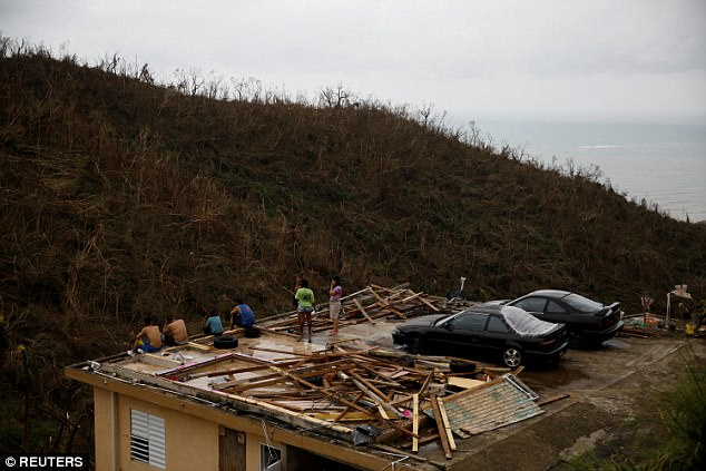 People sit on the roof of a damaged house after the area was hit by Hurricane Maria in Yabucoa, Puerto Rico, on Friday