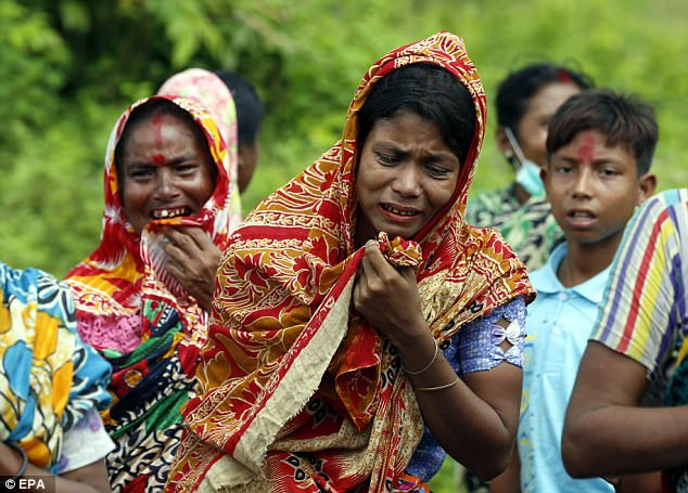 Hindu women weep over the decomposing bodies of relatives who they believe were killed by members of a militant Rohingya organisation