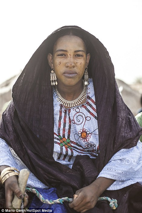 Attraction: Men and women pull on traditional clothing and paint their faces before taking part in a courtship ritual in Niger