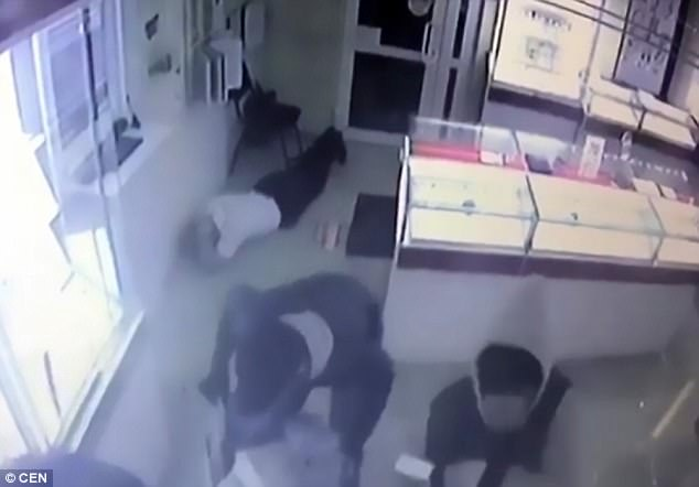 The thugs burst into the St Petersburg store and make a security guard lie flat on the floor