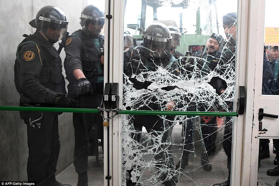Spanish Guardia Civil officers smash down the door of a polling station where the Catalan president Carles Puigdemont was due to vote in Sarria de Ter