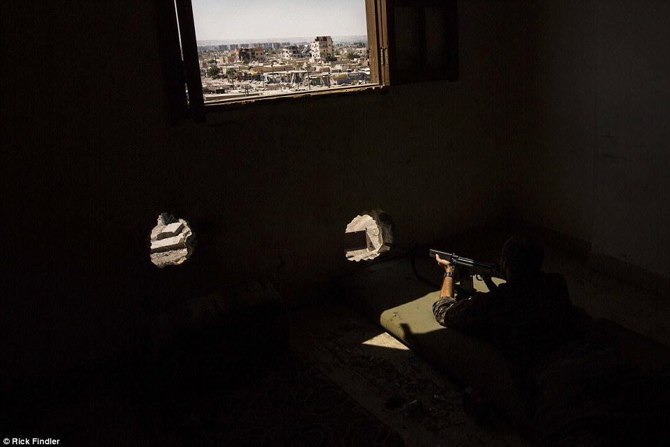 Macer waits patiently as he looks out from a tower block in the search of ISIS militants