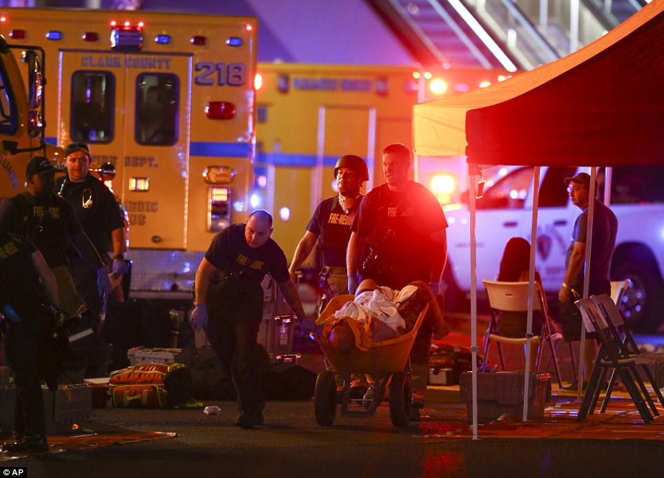 A wounded person is walked in on a wheelbarrow as Las Vegas police respond to the active shooter situation