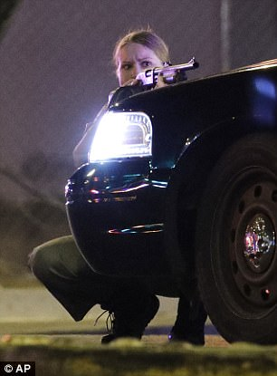A police officer takes cover behind a police vehicle during the shooting near the Mandalay Bay resort and casino